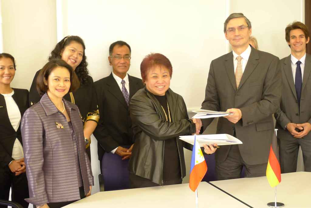 Commissioner Kim Jacinto-Henares of the Bureau of Internal Revenue and Mr. Wolfgang Lasars of the German Federal Ministry of Finance exchange initialed copies of the tax agreement. Joining Ms Henares in the Philippine delegation are, (L-R) Atty. Charadine Bandon, Ambassador Maria Cleofe Natividad, Atty. Marissa Cabreros, and Undersecretary Carlo Carag.