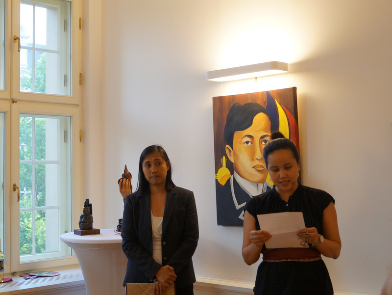 "To set the mood, Second Secretary and Consul Rona Beth Goce (left) read excerpts from Jose Rizal´s poem, ""To the Flowers of Heidelberg"" in English while First Secretary and Consul Catherine Rose Torres delivered excerpts in Filipino. At the background, Ronna Manansala's ""Rizal."""