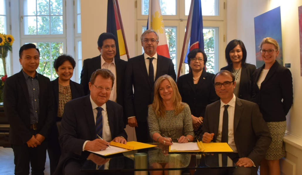 Mr. Grundke of Knauf and Ms. Laibachs and Mr. Helsper of DEG (1st row, L-R) sign the agreement in the presence of Ambassador Thomeczek and the PTIC-Berlin team.